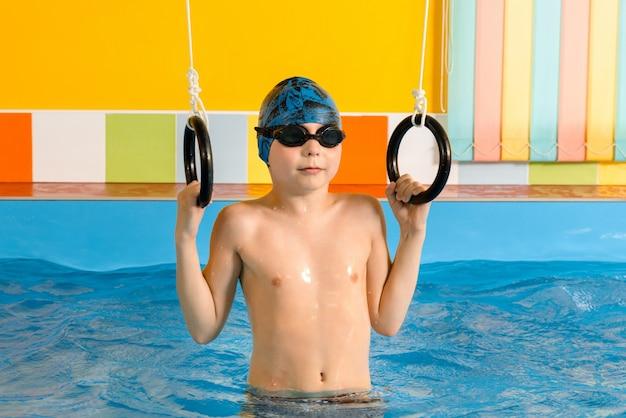 Ребенок в бассейне, упражнения со спортивными кольцами Premium Фотографии