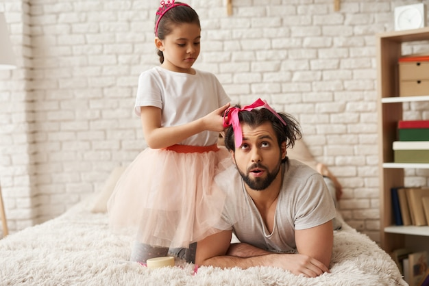 Child is braiding fathers hair Premium Photo