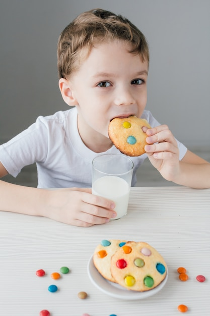 The child is happy to eat homemade biscuits with milk Premium Photo