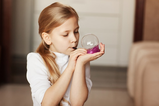 The child is holding a toy called mucus, the child is having fun and experimenting. Premium Photo