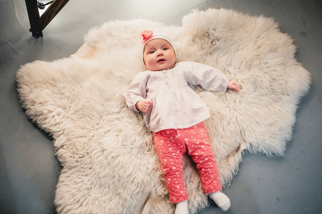 The child is lying on a woolen carpet and smiles at the camera Premium Photo