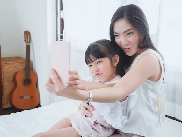 The child is playing in bed with her mother Premium Photo
