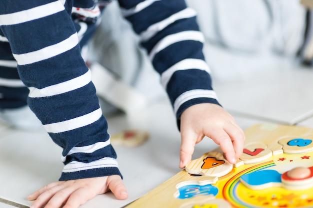 Un bambino sta giocando con un puzzle orologio in legno Foto Gratuite