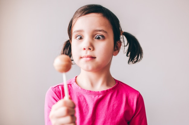 Ребенок изолирован на стене. держите в руке разноцветный леденец и посмотрите на него. вкусный сладкий леденец. серьезная сосредоточенная девушка. Premium Фотографии