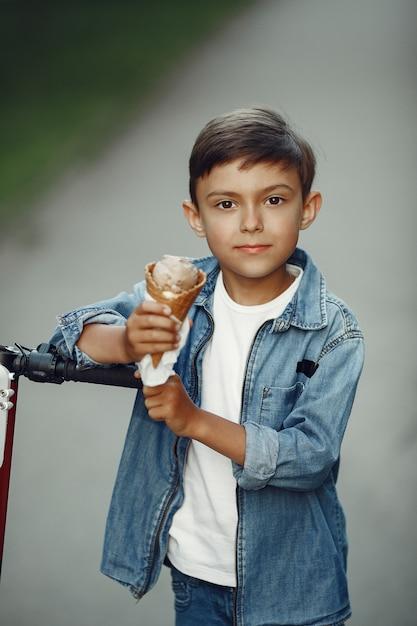 Bambino sul motorino di scossa nel parco. i bambini imparano a pattinare sul roller. ragazzino che pattina sulla soleggiata giornata estiva. Foto Gratuite
