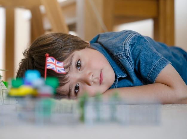 Ребенок лежит на ковре, отдыхая и играя с солдатами и игрушкой-статуэткой, обрезанный выстрел, ребенок смотрит на свои пластиковые игрушки Premium Фотографии