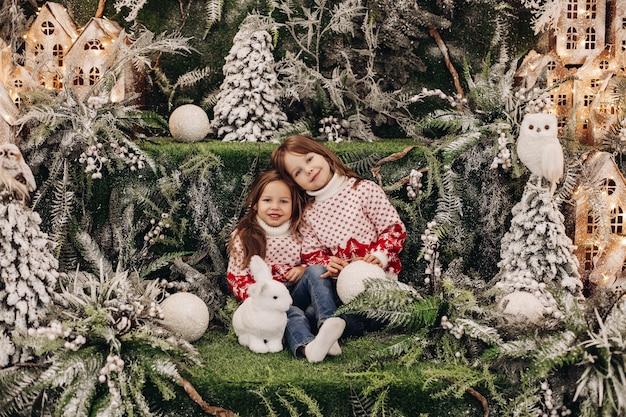 Bambino appoggiato a sua sorella, seduto vicino a un coniglio giocattolo tra gli alberi di natale Foto Gratuite