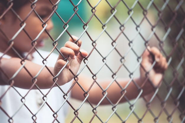 Child little girl hand holding steel mesh in vintage color tone Premium Photo