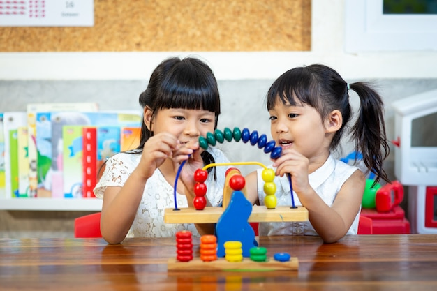 Child little girl playing wooden toys Premium Photo