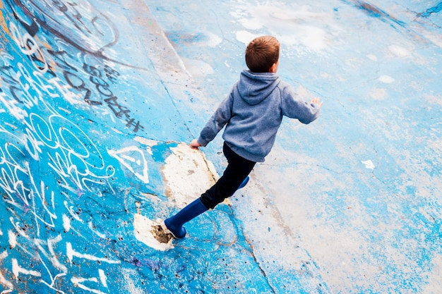 Child loitering inside an abandoned skating area, painted blue, and imagining able to skate. Premium Photo