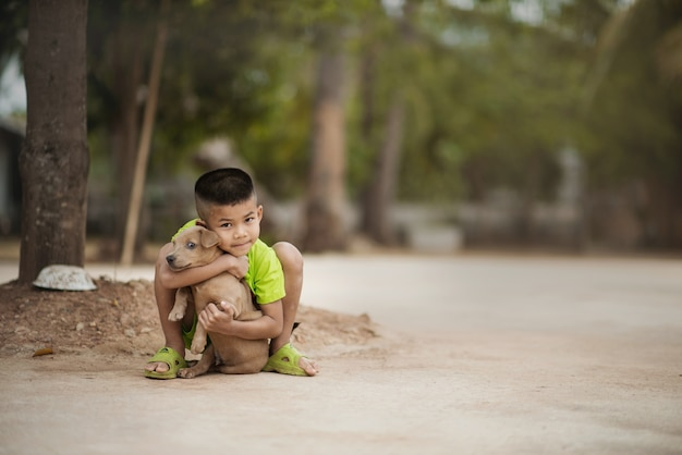 Child lovingly embraces his pet dog Premium Photo