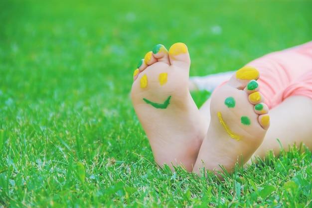 Child lying on green grass. kid having fun outdoors in spring park. Premium Photo