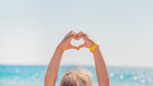 Child makes a heart with her hands Premium Photo
