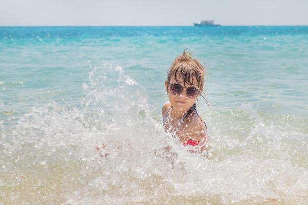 Child makes spray on the sea Premium Photo
