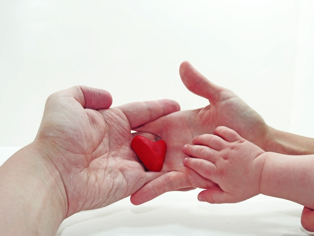 Child, mother and father hand with heart made from play clay Premium Photo