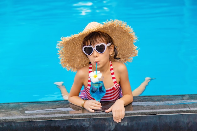 A child near the pool drinks a cocktail. Premium Photo
