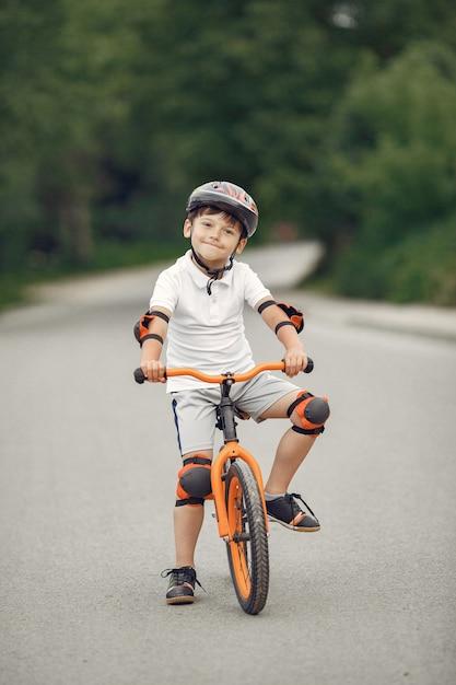 Ребенок на велосипеде на асфальтированной дороге летом. велосипед в парке Бесплатные Фотографии