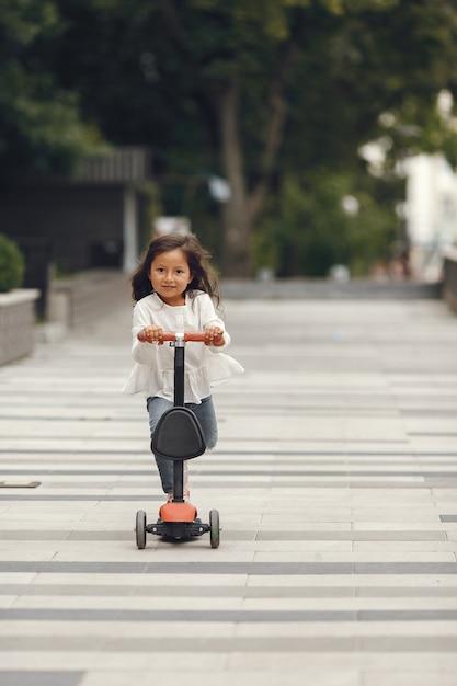 Ребенок на самокате в парке. дети учатся кататься на роликах. маленькая девочка на коньках в солнечный летний день. Бесплатные Фотографии