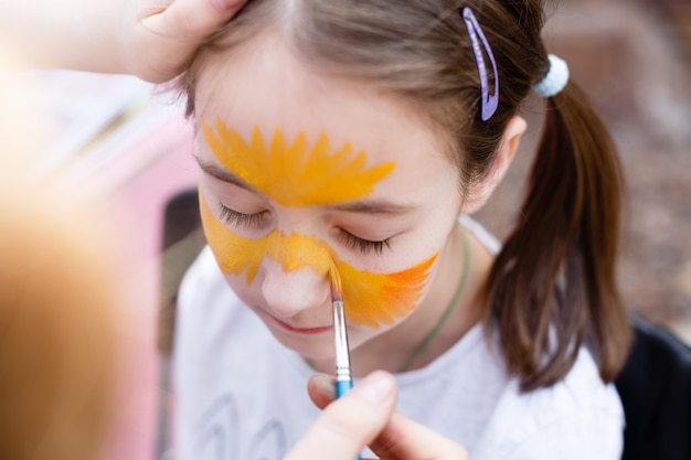 Child painting process on girl's face Premium Photo