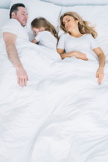 Child and parents sleeping in bed Free Photo