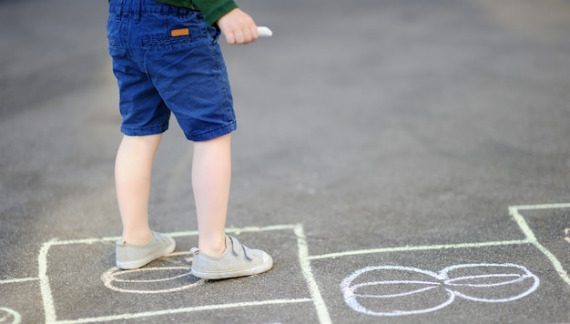 Child playing hopscotch game on playground outdoors on a sunny day Premium Photo