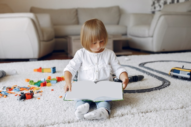 Child playing with book in a playing room Free Photo