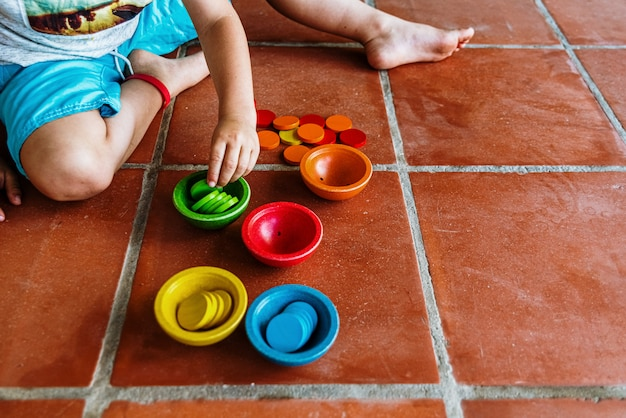 Child playing with a set of colored bowls to fill them, while learning to count by manipulating the educational material. Premium Photo