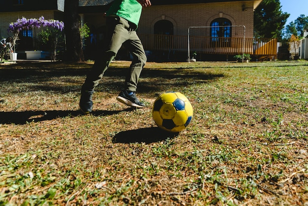Child playing with a soccer ball in the yard of his house in the sun. Premium Photo