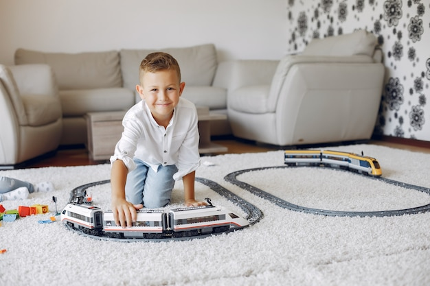 Child playing with toy train in a playing room Free Photo
