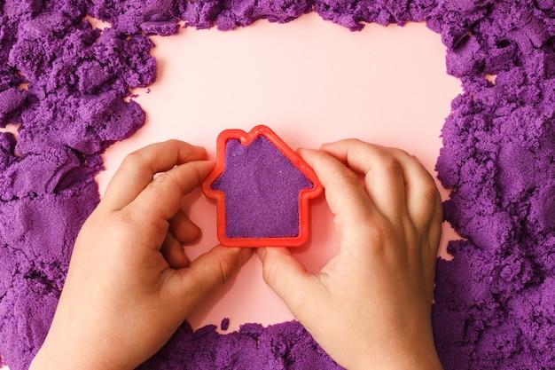 Ребенок играет с фиолетовым кинетическим песком и домашней плесенью Premium Фотографии