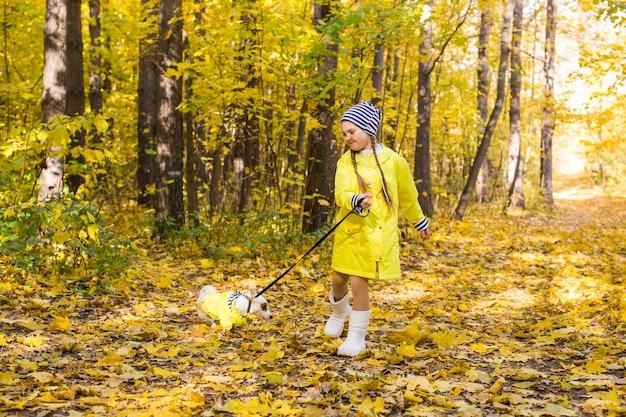 아이 가을 숲에서 잭 러셀 테리어와 함께 재생합니다. 개, 어린이 및 애완 동물과 함께 가을 산책 프리미엄 사진