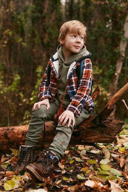 Bambino in posa in natura mentre è seduto su un tronco d'albero Foto Gratuite