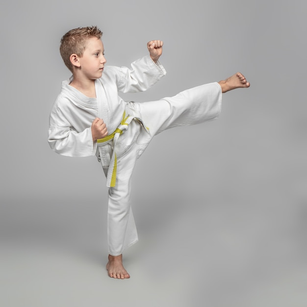 Child practicing karate in kick position. studio shot. Premium Photo