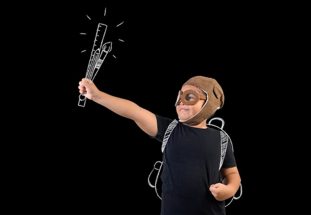 Child pretending to be a superhero and hold school supplies. Free Photo