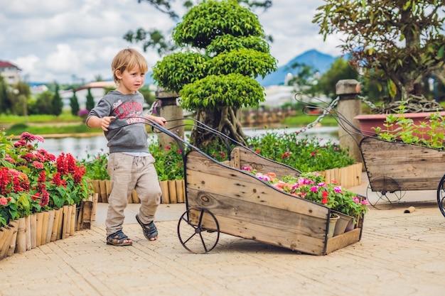 庭でホイールトロリーを押す子供 Premium写真