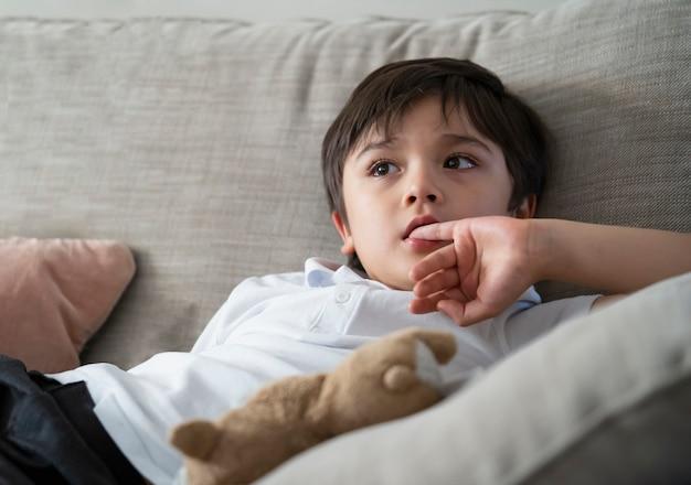 彼の口に指を入れている子供。テレビを見ながら指の爪を噛む男子生徒、感情的な子供の肖像画、ソファに座って考えている顔や緊張した少年 Premium写真