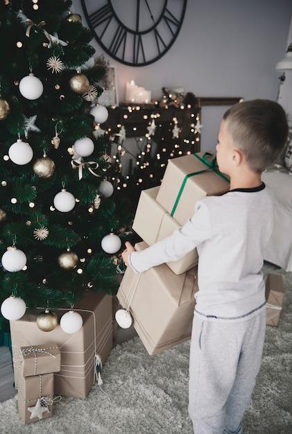 크리스마스 트리 아래 선물을 퍼 팅하는 아이 무료 사진