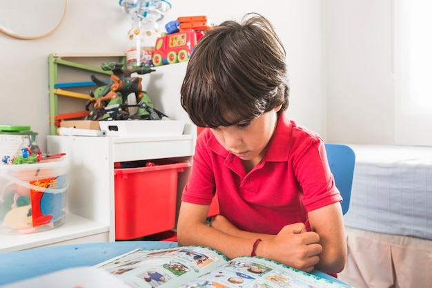 Child reading book at table Free Photo