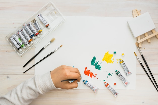Child's hand painting on white paper with paint brush over wooden desk Free Photo