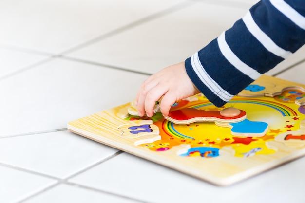La mano di un bambino che gioca con un puzzle orologio in legno in soft focus Foto Gratuite