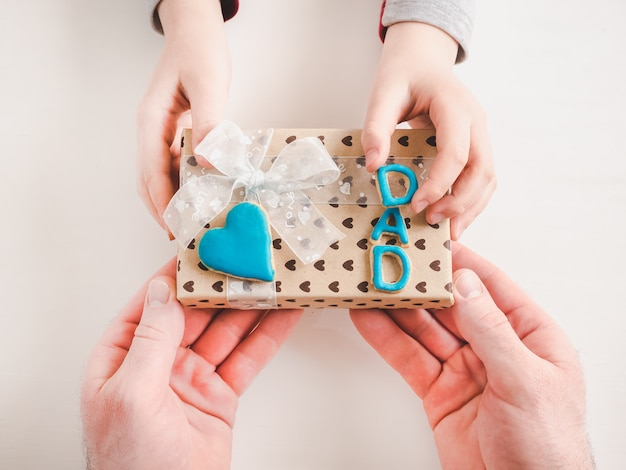 Child's hands and a beautiful gift box Premium Photo