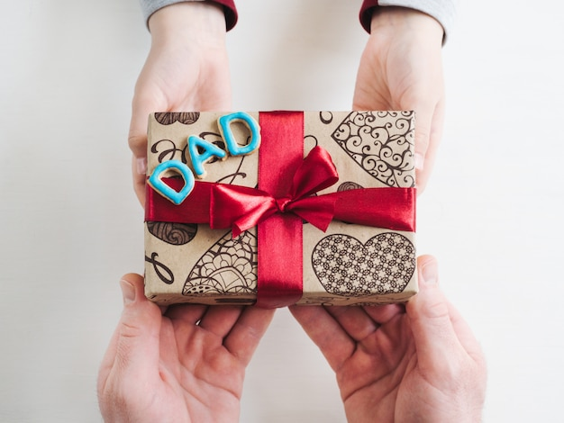 Child's hands and a beautiful gift box, Premium Photo