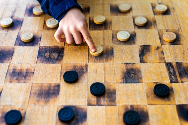 Child's hands moving pieces of checkers game, concepts of struggle Premium Photo