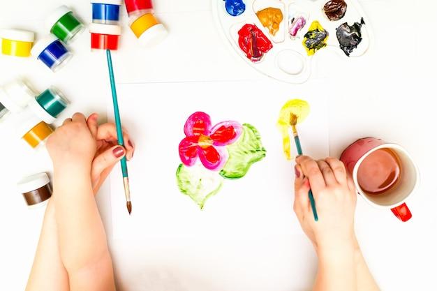Child's hands painting a flower Premium Photo
