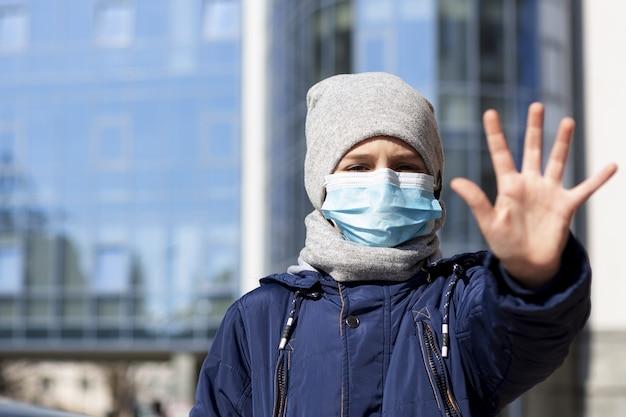 外の医療マスクを着用しながら手を示す子 無料写真