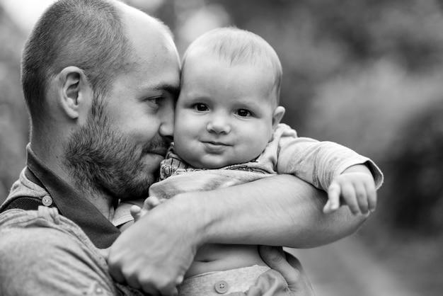 아이는 아빠의 어깨에 앉아 웃고. 흑백 사진 프리미엄 사진