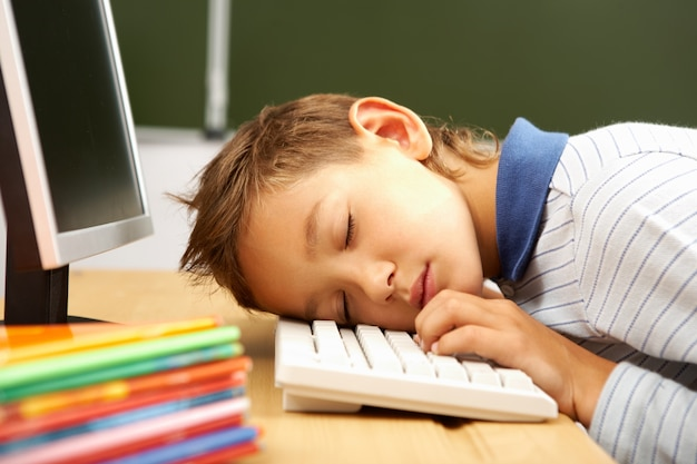 Child sleeping on computer keyboard Free Photo