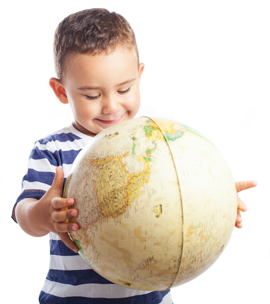 Child smiling with a globe Free Photo