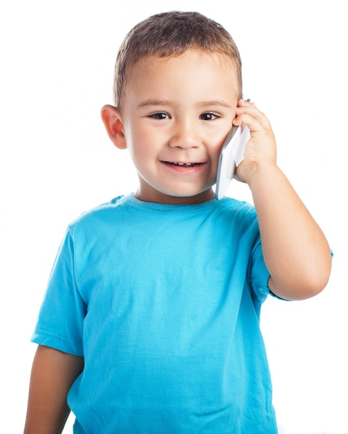 Child smiling with a phone in his ear Free Photo