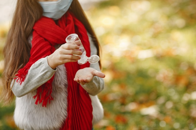 Bambino in piedi nella sosta di autunno. tema coronavirus. ragazza in una sciarpa rossa. il bambino usa l'antisettico. Foto Gratuite